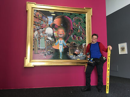 Elizabeth standing in front of a painting she installed